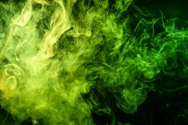 Abstract Art Colored  Green Smoke On Black Isolated Background. Stop The Movement Of Multicolored Sm