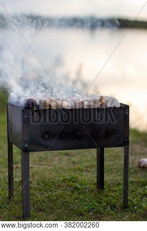 Barbecue On The Lake On Skewers And Barbecue With Coals And Smoke.