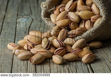 Pistachio In Nutshell On Wooden Rustic Backdrop In Wooden Shovel, Composition Of Pistachios Great Fo