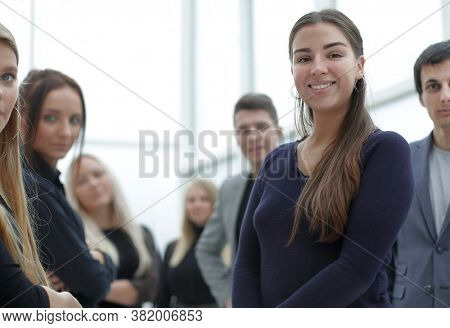 confident young business woman standing among her colleagues
