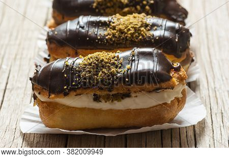 Eclairs With Pistachio And Black Chocolate And White Chocolate With Custard On Wooden Background And