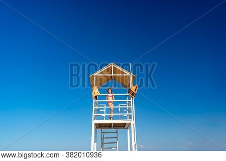 A Teenage Girl Stands On A Lifeguard Tower On The Beach Against A Cloudless Sky.