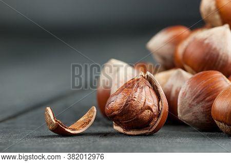 Hazelnuts, Filbert On Black Wooden Backdrop. Heap Or Stack Of Shelled Hazelnuts. Hazelnut Background