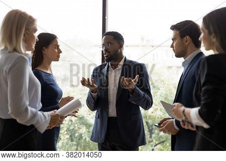 Black Team Leader Talking To Diverse Subordinates At Informal Meeting