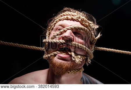 Photo Of Binded Tattooed Screaming Man With Rope On Face