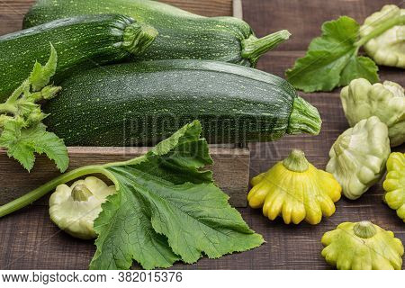 Squash (zucchini) In Wooden Box, Pattypan Squash On Wooden Surface, Green Leaves Of Vegetables.