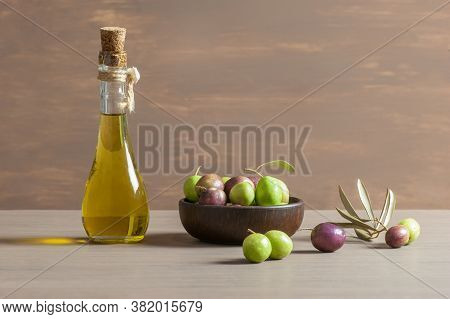 Glass Bottle Of Olive Oil And Wooden Breakfast Bowl With Raw Turkish Olive Seeds And Leaves On Woode