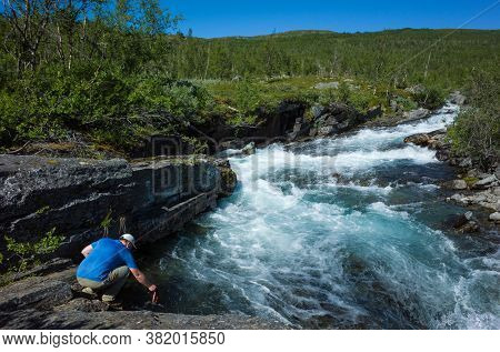 Summer trekking in Sweden. Man fills bottle with clear drinking water from river Abiskojokk in Abisko National Park in northern Sweden, Scandinavian nature. Sunny day