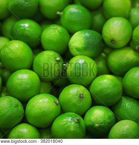 Many Fruits Of Green Ripe Refreshing Limes Are Lying In The Grocery Store. A Rich Harvest Of Fruit.