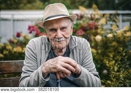 Portrait Of A Smiling And Confident Older 87-year-old Handsome Man In A Hat With A Mustache. Happy A