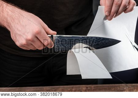 Man Testing Sharpness Of Knife By Cutting A Thin Sheet Of Paper