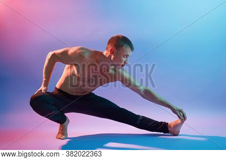 Man Performing Yoga, Doing Exercising For Stretching, Topless Guy Practicing Yoga Isolated Over Neon