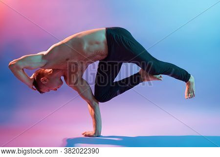 Athletic Muscular Young Man Practicing Yoga Doing Exercises For Body Balance, Standing On One Leg, W