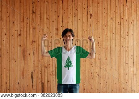 Man Wearing Norfolk Island Flag Color Of Shirt And Standing With Raised Both Fist On The Wooden Wall