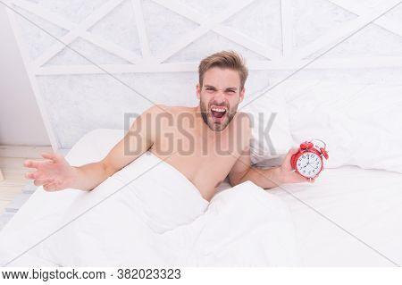 Man Sleeping Bed White Bedclothes And Red Alarm Clock, Feeling Irritated Concept.