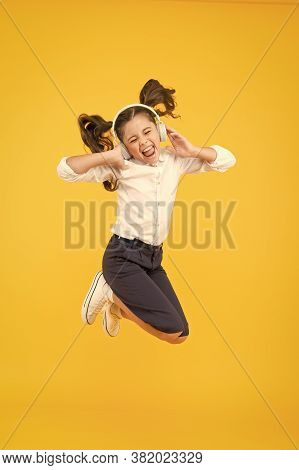 Music Of Happiness. Happy Little Child Jumping With Happiness On Yellow Background. Happy Small Girl