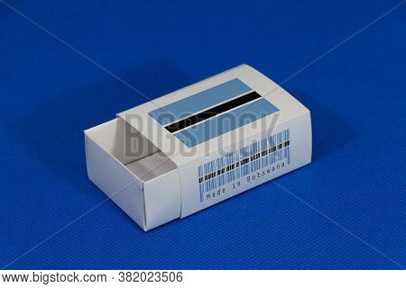 Botswana Flag On White Box With Barcode And The Color Of Nation Flag On Blue Background, Paper Packa