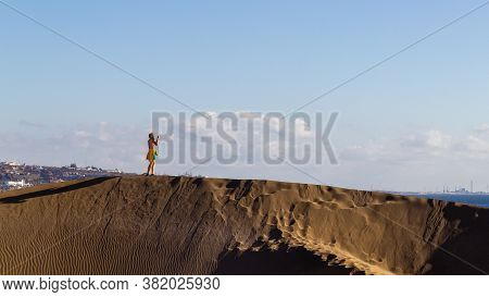 Girl Taking A Photo From A High Dune. The Dunes Are Part Of The Famous Maspalomas Dunes In Gran Cana