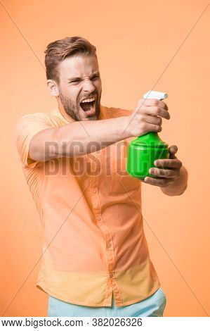 Macho Hold Plastic Spray Bottle As Gun Yellow Background. Guy With Water Spray In Hand Pretend Shoot