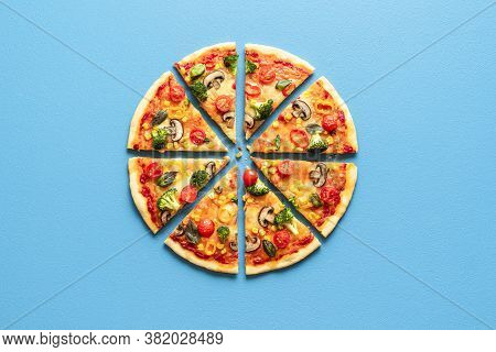 Top View With A Sliced Pizza Primavera On A Blue Table. Vegetarian Pizza Flat Lay. Sliced Pizza Isol