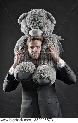 I Am So Sorry. Man Carries Giant Teddy Bear On Neck, Dark Background. Reunion Gift Concept. Guy Calm