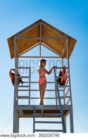 Rear View. A Teenage Girl Stands On A Lifeguard Tower On The Beach Against A Cloudless Sky.