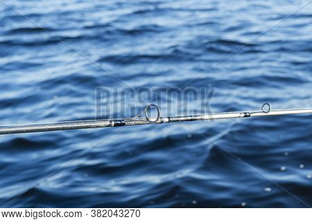 Fishing Rod Spinning With The Line Close-up. Fishing Rod Over Blue Ocean. Fishing Rod Rings.tackle.