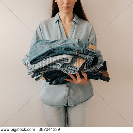 Unrecognizable Woman Holds Stack Of Lot Jeans Pants On White Background. Caucasian Woman With Long B