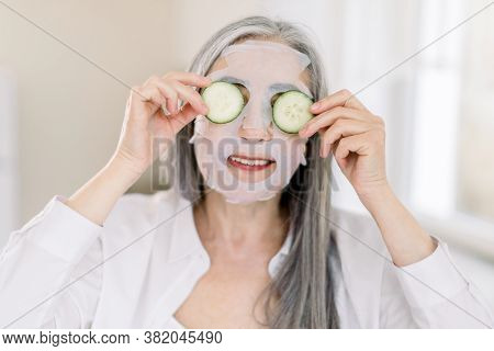 Smiling Gray Haired Senior Woman At Home, With Facial Sheet Anti-aging Mask On Face Skin, Holding Fr