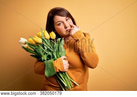 Beautiful plus size woman holding romantic bouquet of natural tulips flowers over yellow background Pointing to the eye watching you gesture, suspicious expression