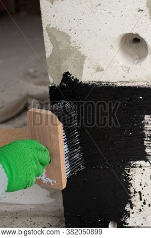 Roofers Hand In Green Mittens Holding A Brush