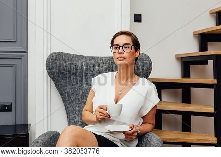 Beautiful Mid Adult Woman Drinking Coffee In Her Apartment And Looking Away