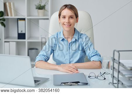 Young attractive businesswoman with blond hair and toothy smile looking at you while sitting by desk in front of camera and working in office
