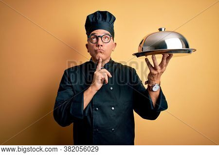 Middle age handsome grey-haired waiter man wearing cooker uniform and hat holding tray Thinking concentrated about doubt with finger on chin and looking up wondering
