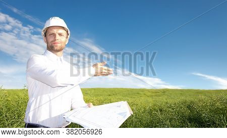Builder Wearing In White Helmet With Blueprints Shows The Prospective Construction Site On Green Fie