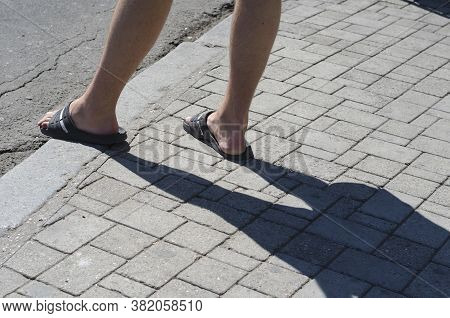 Naked Male Feet In Flip Flops At The Edge Of The Sidewalk. A Mature Man With Hairy Legs Stands At Th
