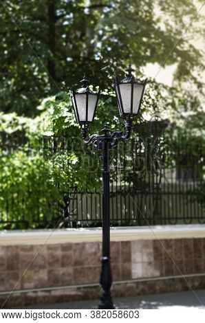 Vintage Lamppost On A City Street. Black Metal Lamppost Against The Background Of A Forged Fence And