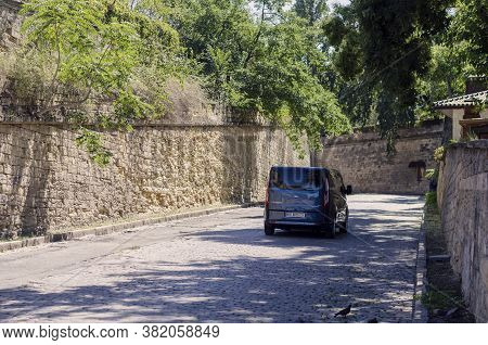 Mykolayiv, Ukraine - August 17, 2020: Ford Transit Minibus Drives Along An Empty City Street With St