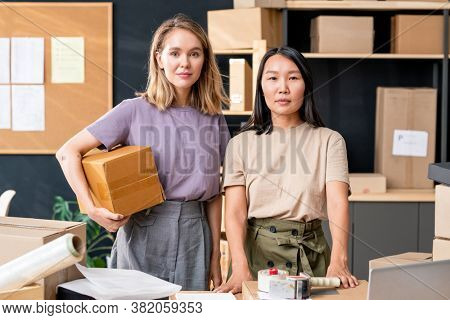 Two young female workers of online shop office standing by table against shelves with packed boxes and noticeboard with documents