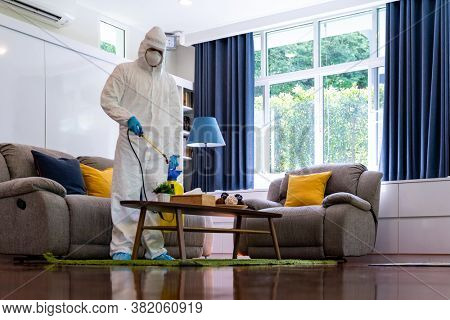 Asian Medical staff in personal protective equipment PPE suit spraying disinfectant spray for coronavirus COVID-19 in living room. Delivery health care hygiene and disinfection concept