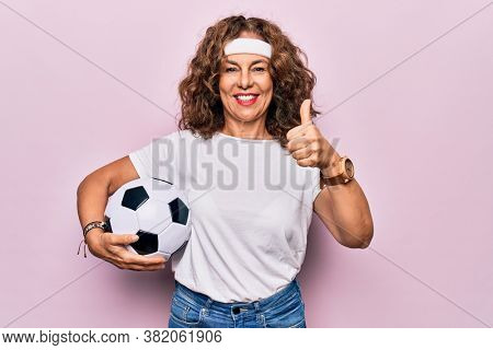 Middle age beautiful sporty woman playing soccer holding football bal over pink background smiling happy and positive, thumb up doing excellent and approval sign