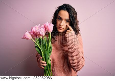 Young beautiful romantic woman with curly hair holding bouquet of pink tulips Pointing to the eye watching you gesture, suspicious expression