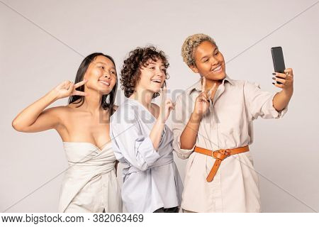 Young Asian, African and Caucasian women in white smart casualwear making selfie while looking in smartphone camera with smiles