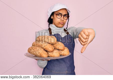Young african american baker woman wearing apron holding wholemeal bread with cereal with angry face, negative sign showing dislike with thumbs down, rejection concept