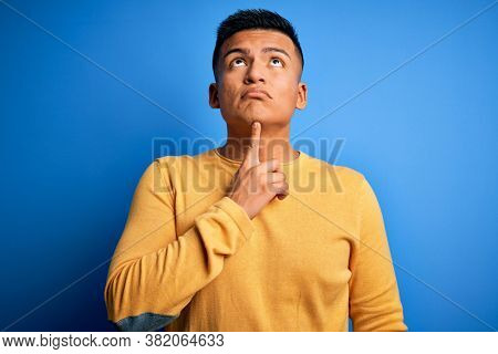 Young handsome latin man wearing yellow casual sweater over isolated blue background Thinking concentrated about doubt with finger on chin and looking up wondering