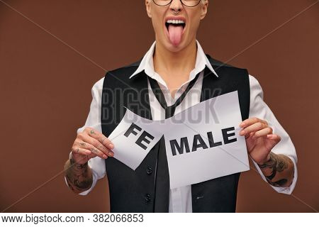 Aggressive woman in formalwear showing her tongue and tearing off syllable fe from word female on paper so that it became male
