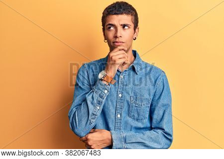 Young african amercian man wearing casual clothes thinking concentrated about doubt with finger on chin and looking up wondering