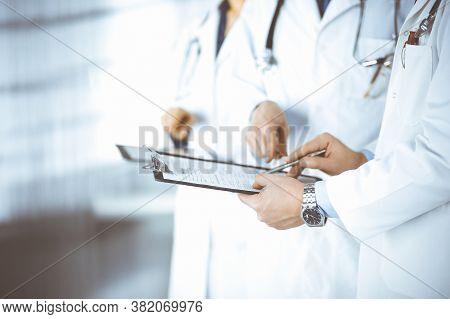 Group Of Unknown Doctors, Men And A Woman, With Stethoscopes, Discuss Medical Exam Resoults, Using A