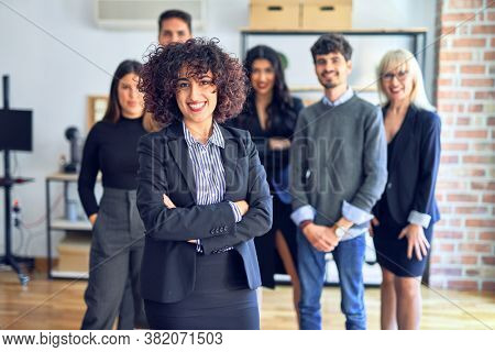 Group of business workers smiling happy and confident. Posing together with smile on face looking at the camera, young beautiful woman with crossed arms at the office