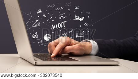 Businessman working on laptop with AUDIT inscription, modern business concept